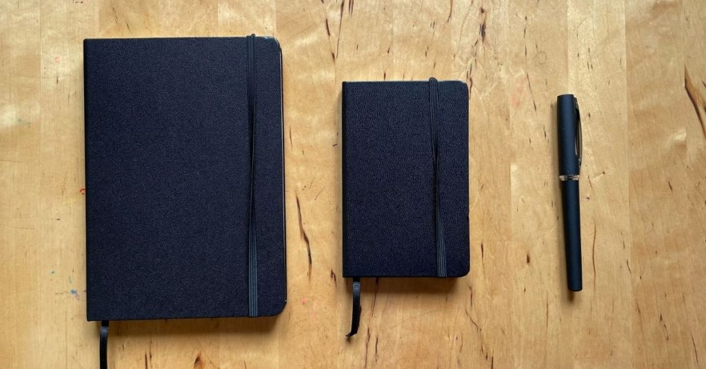 Two diaries and a pen on a table
